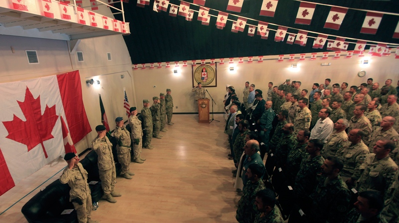 Afghan officials and NATO troops salute during a national anthem in a transfer of command authority ceremony in Kandahar airbase in Afghanistan, Thursday, July 7, 2011. (AP / Rafiq Maqbool)