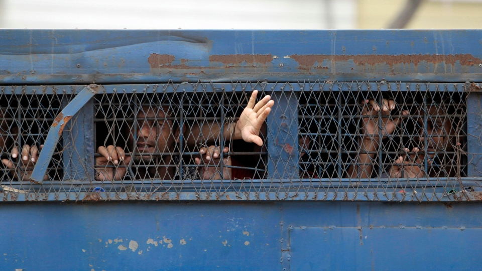 Bangladeshi border guards look out through the window of a prison van as they leave a special court after a verdict in Dhaka, Bangladesh, Tuesday, Nov. 5, 2013. (AP / A.M. Ahad)