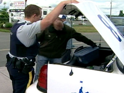 Police carry away the sixth foot, found in a size 10 shoe from a beach on Vancouver Island on Wednesday, June 18, 2008.