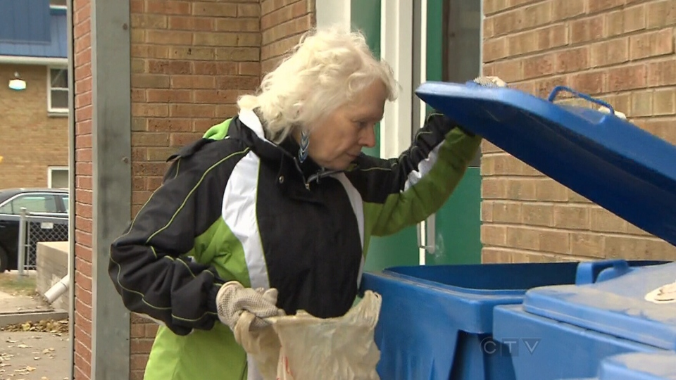 Joey-Jane Hylton looks for cans in a recycling bin to supplement her pension in Winnipeg, on Tuesday, Nov. 5, 2013.