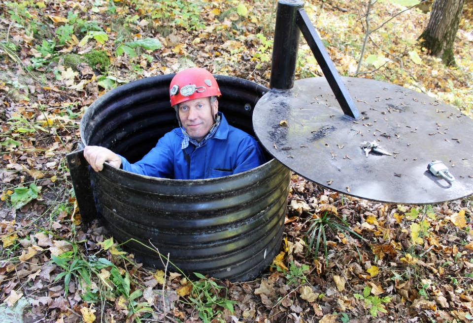 In this Oct. 10, 2013, photo, John Ackerman poses in a shaft entrance to his Temple of Doom, one of the 37 caves on his property near Spring Valley, Minn.  (AP Photo/Jeff Baenen)