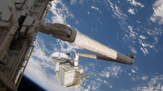 Backdropped by the Earth's oceans, the Space Shuttle Endeavour's Canadarm, controlled by Canadian astronaut Julie Payette, is about to hand off the Integrated Cargo Carrier (ICC) to the International Space Station