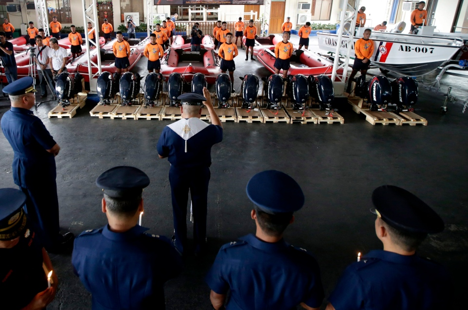 Philippine Coast Guard Chief Rear Adm. Rodolfo Isorena, left, witnesses the blessing of newly-acquired rubber boats following blessing ceremony Wednesday, Nov. 6, 2013 in Manila, Philippines. (AP / Bullit Marquez)