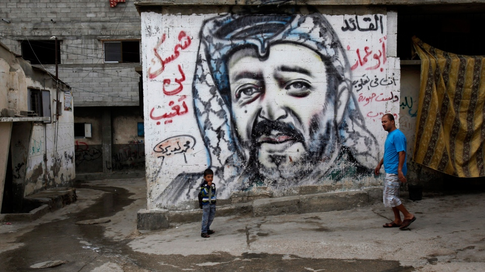 Palestinians walk past a mural depicting late Palestinian leader Yasser Arafat at Shati Refugee Camp, in Gaza City, Thursday, Nov. 7, 2013. (AP / Adel Hana)