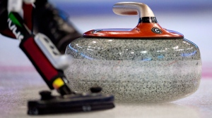 A curling stone is swept down the ice during the afternoon draw at the Tim Hortons Brier in Edmonton, Alta. Thursday, March 7, 2013. (THE CANADIAN PRESS/Jonathan Hayward)