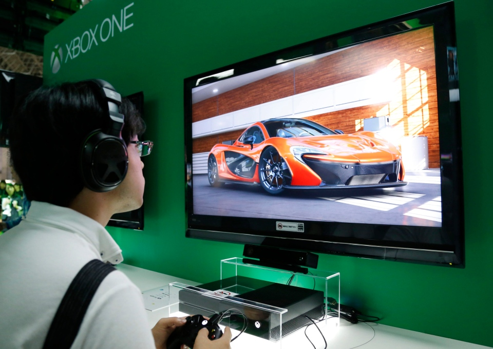 In this Sept. 19, 2013 file photo, a visitor tries Microsoft Xbox One during the Tokyo Game Show 2013 in Makuhari near Tokyo. (AP Photo/Koji Sasahara)