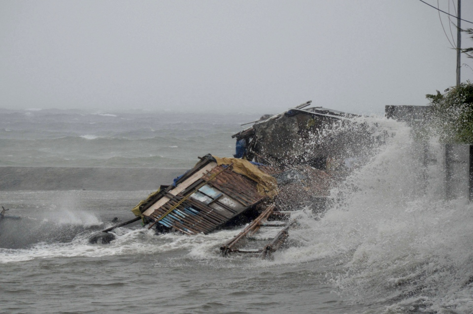 A house is engulfed by the storm surge brought about by powerful typhoon Haiyan that hit Legazpi city, Albay province about 520 kilometres south of Manila, Philippines, Friday Nov. 8, 2013. (AP / Nelson Salting)