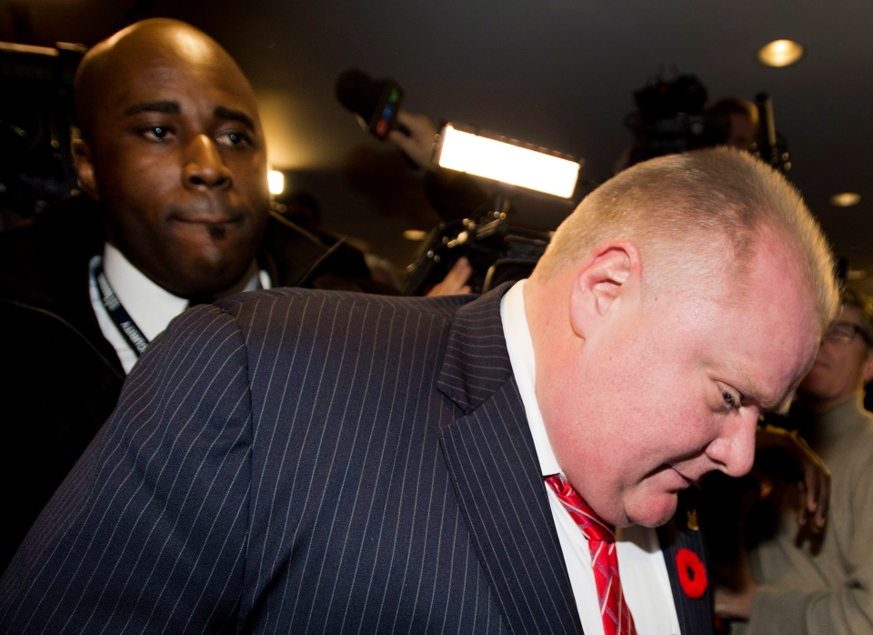 Toronto Mayor Rob Ford pushes through the mob of media with security and his new driver, left, as he arrives at his office in Toronto on Friday, Nov. 8, 2013. (Nathan Denette / THE CANADIAN PRESS)