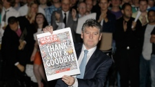 News of the World tabloid newspaper Editor, Colin Myler poses with a front page of the last edition as he leads his staff out of the headquarters of News International, the publisher of News of the World newspaper, in London, Saturday, July 9, 2011. (AP / Sang Tan)