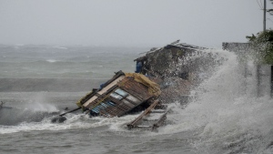 A house is engulfed by the storm surge brought about by powerful typhoon Haiyan that hit Legazpi city, Albay province, south of Manila, Philippines. Friday Nov. 8, 2013.  (AP Photo/Nelson Salting)