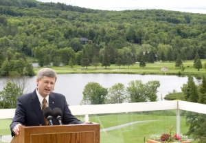 With Peninsula Lake as the background, Prime Minister Stephen Harper speaks to reporters from Deerhurst Resort in Huntsville, Ont., approximately 200 km north of Toronto. The 2010 G8 meetings will be held in the area. (Adrian Wyld / THE CANADIAN PRESS)