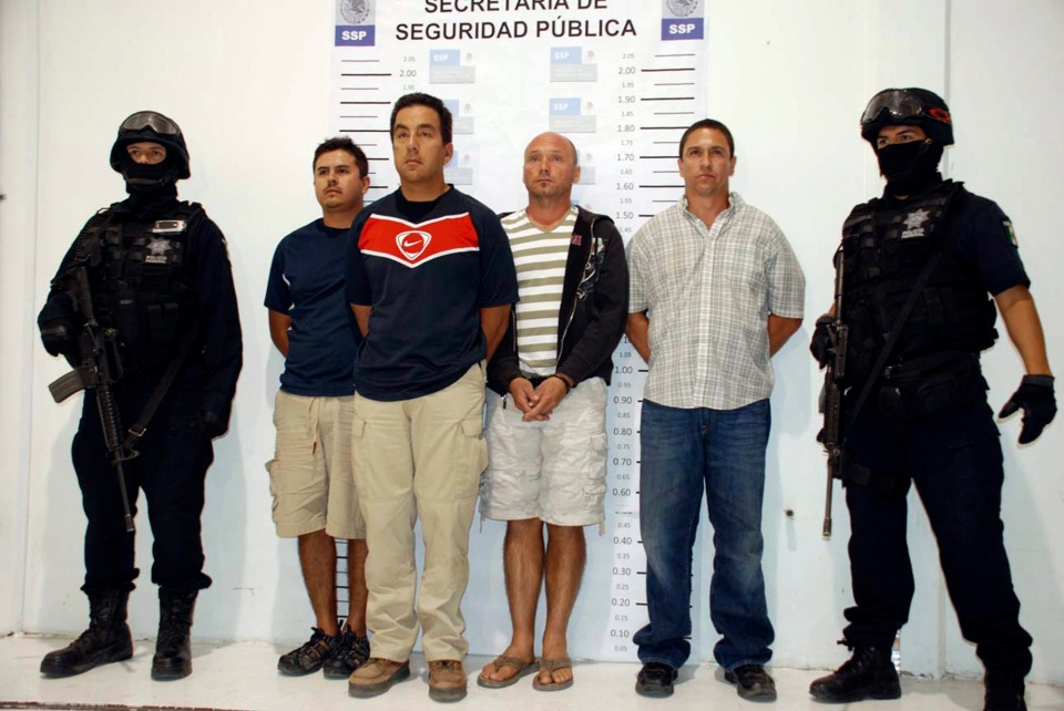 Police officers escort Pavel Kulisek, third from right, and three other detainees at an undisclosed location in Mexico. (Mexico Attorney General's Office)