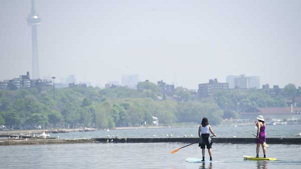 Two women use paddle boards on Lake Ontario just off the boardwalk along Lakeshore Blvd., in Toronto on Tuesday, May 31, 2011. The temperature on the day was expected to hit 31C. (Nathan Denette / THE CANADIAN PRESS)