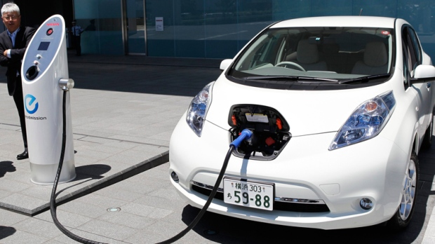 Nissan Motor Co. chief vehicle engineer Hidetoshi Kadota demonstrates a quick charge of a Nissan Leaf by a solar-assisted EV charging system at Nissan's global headquarters in Yokohama, Japan, Monday, July 11, 2011. (AP / Koji Sasahara)