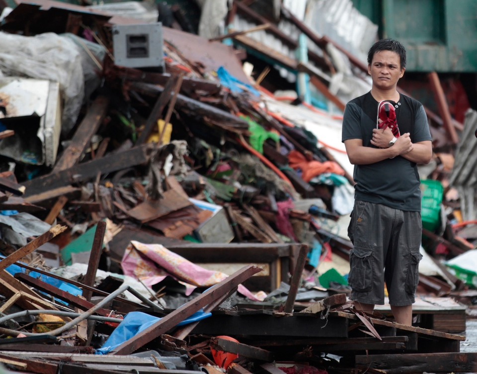 A resident looks at houses damaged by typhoon Haiyan, in Tacloban city, Leyte province central Philippines on Sunday, Nov. 10, 2013. (AP / Aaron Favila)
