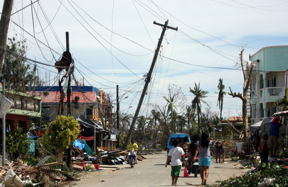 Residents walk past the devastation caused by Typhoon Haiyan in Daanbantayan town, north Cebu, central Philippines on Sunday, Nov. 10, 2013. (AP / Chester Baldicantos)