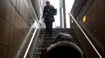 A woman walks down the steps into a subway station as snow falls inToronto on Friday January 25, 2013 (THE CANADIAN PRESS / Chris Young)