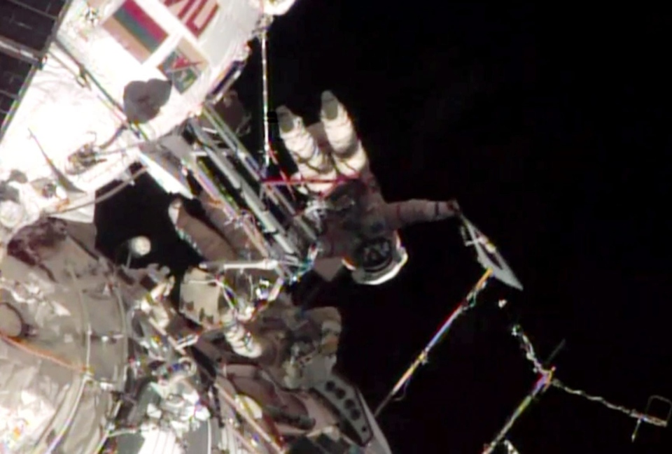 This screen image taken from NASA shows the Sochi Olympic torch being held during a spacewalk on Saturday, Nov. 9, 2013.