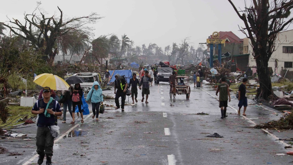 Residents walk past damaged houses in Tacloban city, Leyte province, central Philippines on Sunday, Nov. 10, 2013. (AP / Bullit Marquez)
