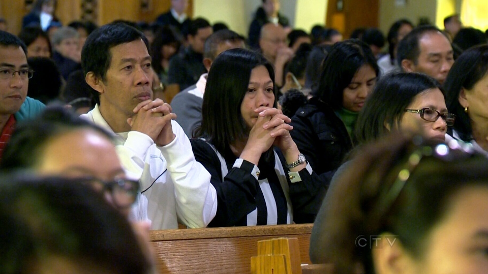 Church members gather to pray for victims affected by Typhoon Haiyan in Montreal on Sunday, Nov. 10, 2013.