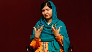 Malala Yousafzai gestures as she speaks to an audience during a discussion of her book, 'I am Malala,' hosted by the John F. Kennedy Library and held at Boston College High School in Dorchester, Mass.,  Saturday, Oct. 12, 2013. (AP / Jessica Rinaldi)