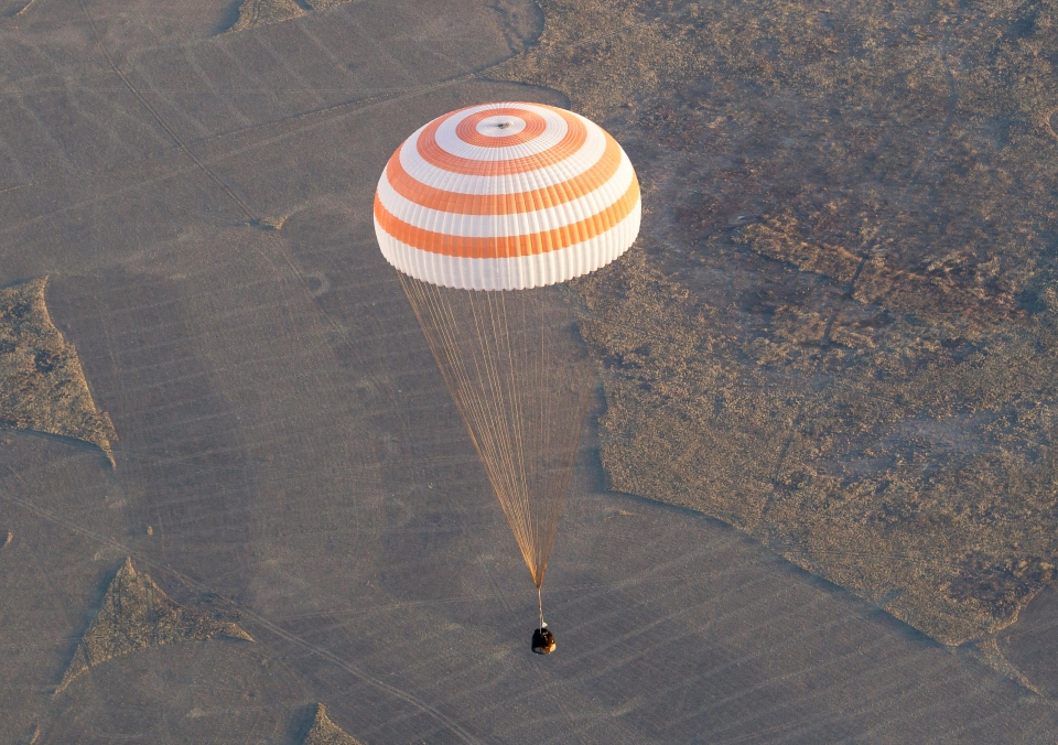 Soyuz TMA-09M capsule carrying the International Space Station (ISS) crew members, Fyodor Yurchikhin of Russia, Karen Nyberg of the United States and Luca Parmitano of Italy, descends with a parachute before landing in a remote area near the town of Zhezkazgan in central Kazakhstan Monday, Nov. 11, 2013. (AP / Shamil Zhumatov)