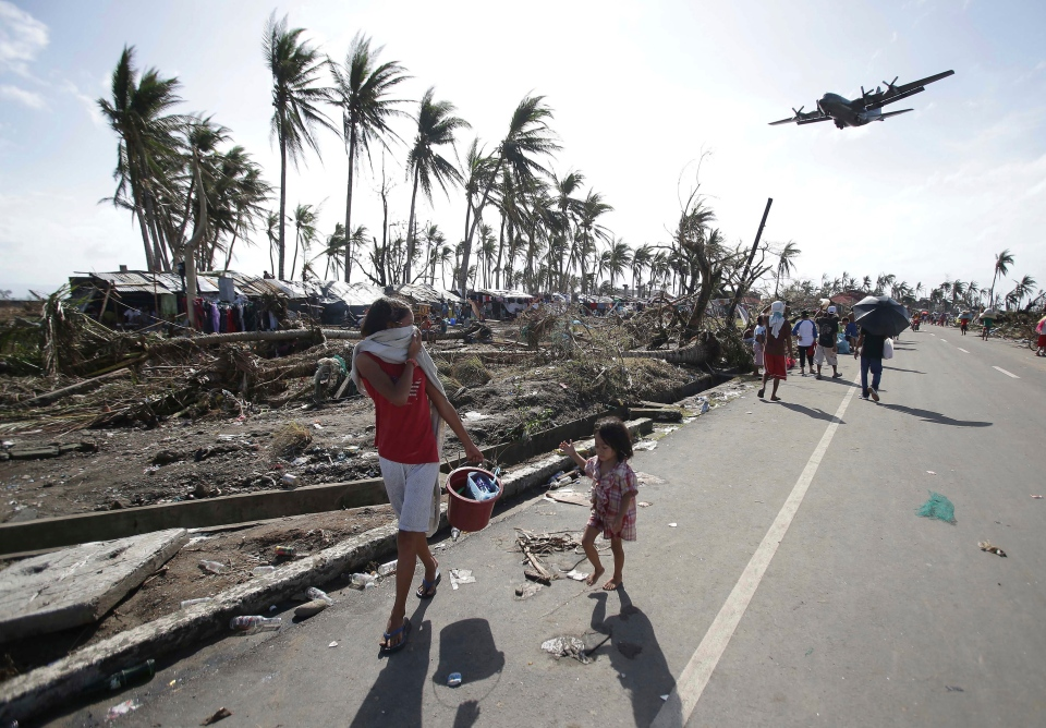 Survivors look up at a military C-130 plane as it arrives at typhoon-ravaged Tacloban city, Leyte province in central Philippines on Monday, Nov. 11, 2013. (AP / Aaron Favila)