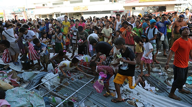 Residents watch as others throw goods from a warehouse in Guiuan, Eastern Samar province, central Philippines, Monday, Nov. 11, 2013. (AP / Ted Aljibe)