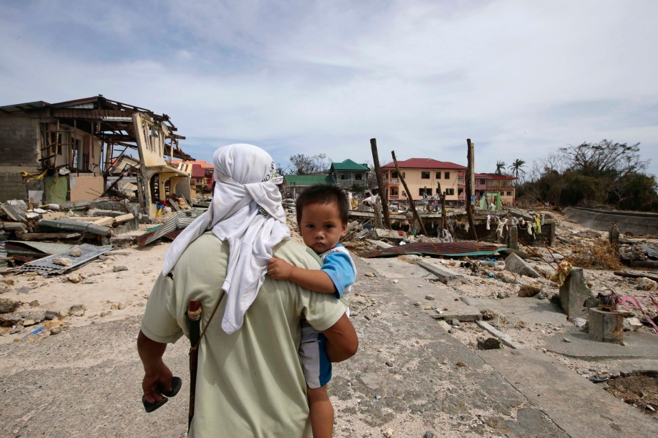 A man walks home with his son  following Friday's devastating typhoon that lashed Hernani township, in eastern Samar province, in the central Philippines, Monday, Nov. 11, 2013. (AP / Bullit Marquez)