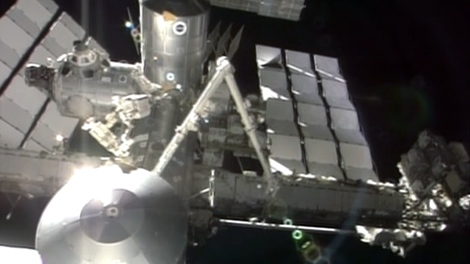Canadarm2, attached to the International Space Station, is used by astronauts during a spacewalk, Tuesday, July 12, 2011.