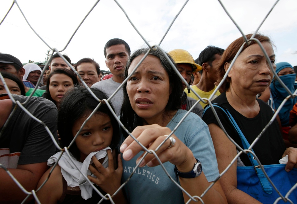 Residents queue up to receive treatment and relief supplies at Tacloban airport Monday Nov. 11, 2013, following Friday's typhoon Haiyan that lashed this city and several provinces in central Philippines. (AP / Bullit Marquez)