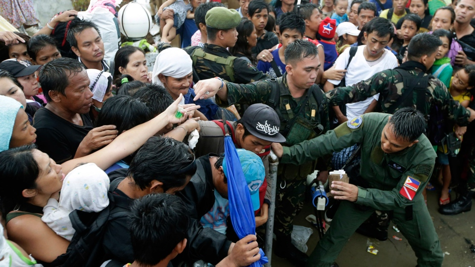 Typhoon survivors jostle to get a chance to board a C-130 military transport plane Tuesday, Nov. 12, 2013, in Tacloban, central Philippines. (AP / Bullit Marquez)
