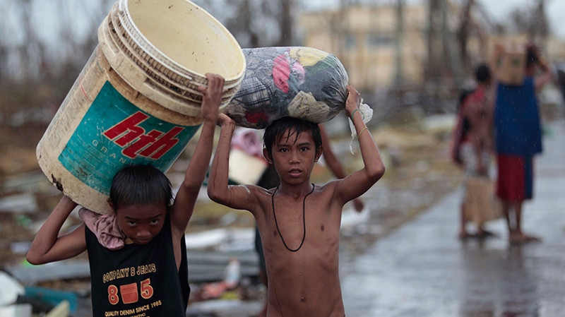 Survivors carry clothes along a road at typhoon-ravaged Tacloban city, Leyte province, central Philippines on Tuesday, Nov. 12, 2013. (AP / Aaron Favila)
