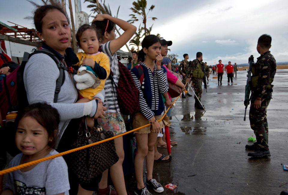 Survivors wait to board a Philippine Air Force C-130 cargo plane at the airport in Tacloban, central Philippines, Tuesday, Nov. 12, 2013. (AP / Vincent Yu)
