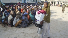 A woman walks after receiving food, money and blankets distributed by the Somali government in Mogadishu, Somalia on Monday July 11, 2011. (AP Photo/Farah Abdi Warsameh)