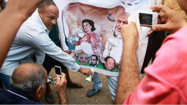 Egyptian protesters surround a poster showing the face of ousted President Hosni Mubarak and his family on a bull face at Tahrir Square in Cairo, Egypt, Monday, July 11, 2011 during the fourth day of protest.  (AP / Amr Nabil)