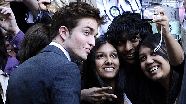 """Actor Robert Pattinson takes pictures with fans at the premiere of """"Water For Elephants"""" at the Ziegfeld Theater on Sunday, April 17, 2011, in New York. (THE CANADIAN PRESS/AP-Peter Kramer)"""