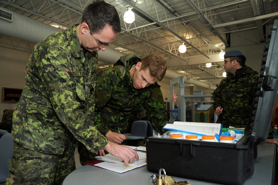 Pharmacists Captain Wayne Clark and Captain Adam Calabrese prepare a nominal list for members of a Disaster Assistance Response Team (DART) prior to their innoculation, in anticipation of a rapid deployment to the Philippine Islands that were ravaged by typhoon Haiyan, at CFB Trenton, Ont. on Nov.11, 2013. (Canadian Forces Combat Camera / Cpl. Darcy Lefebvre)