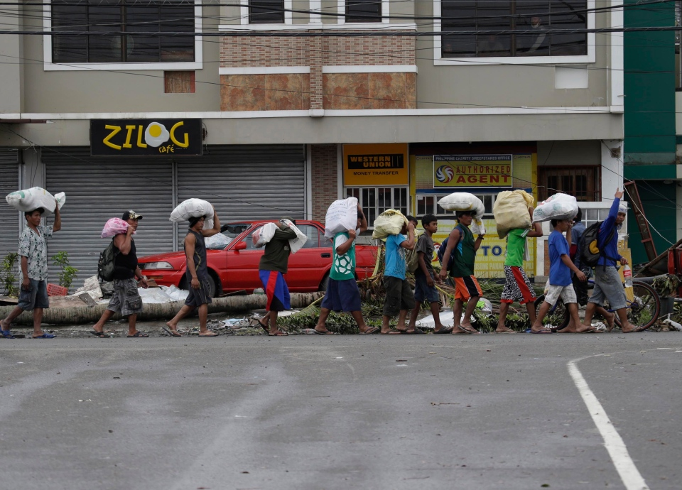 People carry sacks of goods in Tacloban city in Leyte province, central Philippines, Tuesday, Nov. 12, 2013. (AP / Bullit Marquez)