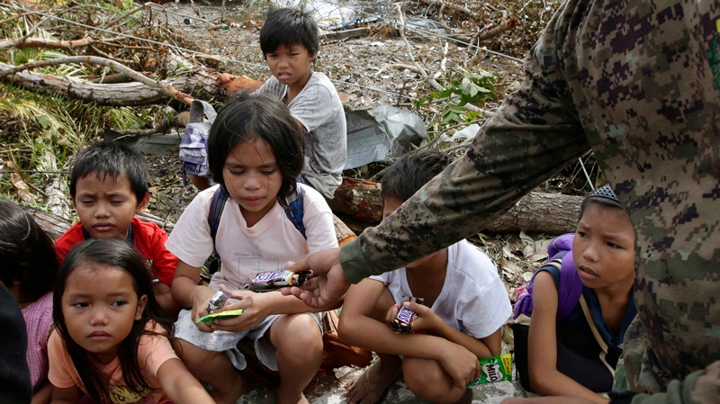 Children, who say they fled when armed men were seen in their village, are given biscuits and chocolates by a police officer while waiting in Tacloban city, Leyte province in central Philippines Wednesday, Nov. 13, 2013. (AP / Bullit Marquez)