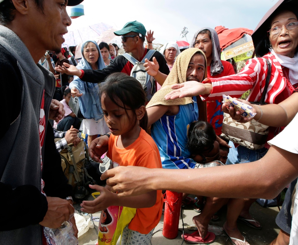 A Good Samaritan, left, hands out biscuits to typhoon survivors as they queue up at Tacloban city airport hoping to be able to board U.S. and Philippine military transport planes Wednesday, Nov. 13, 2013. (AP / Bullit Marquez)