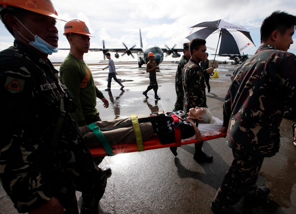 An injured typhoon survivor is carried on a stretcher prior to being airlifted in a military transport plane from the damaged Tacloban airport at Tacloban city, Leyte province in central Philippines, Wednesday, Nov. 13, 2013. (AP / Bullit Marquez)
