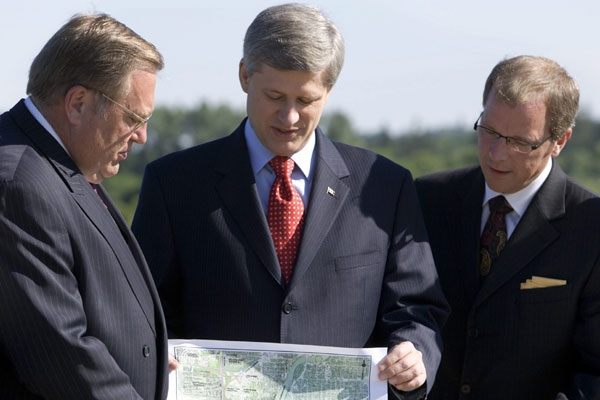 Prime Minister Stephen Harper, centre, looks over an urban bypass roadway planning map with Saskatoon Mayor Don Atchison, left, and Saskatchewan Premier Brad Wall in Saskatoon, Sask., Friday, June 20, 2008. (Geoff Howe/ THE CANADIAN PRESS)
