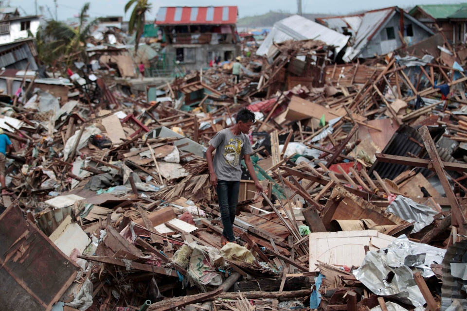 A Filipino man walks among debris from damaged homes at typhoon-hit Tacloban city, Leyte province, central Philippines on Wednesday, Nov. 13, 2013. (AP / Aaron Favila)