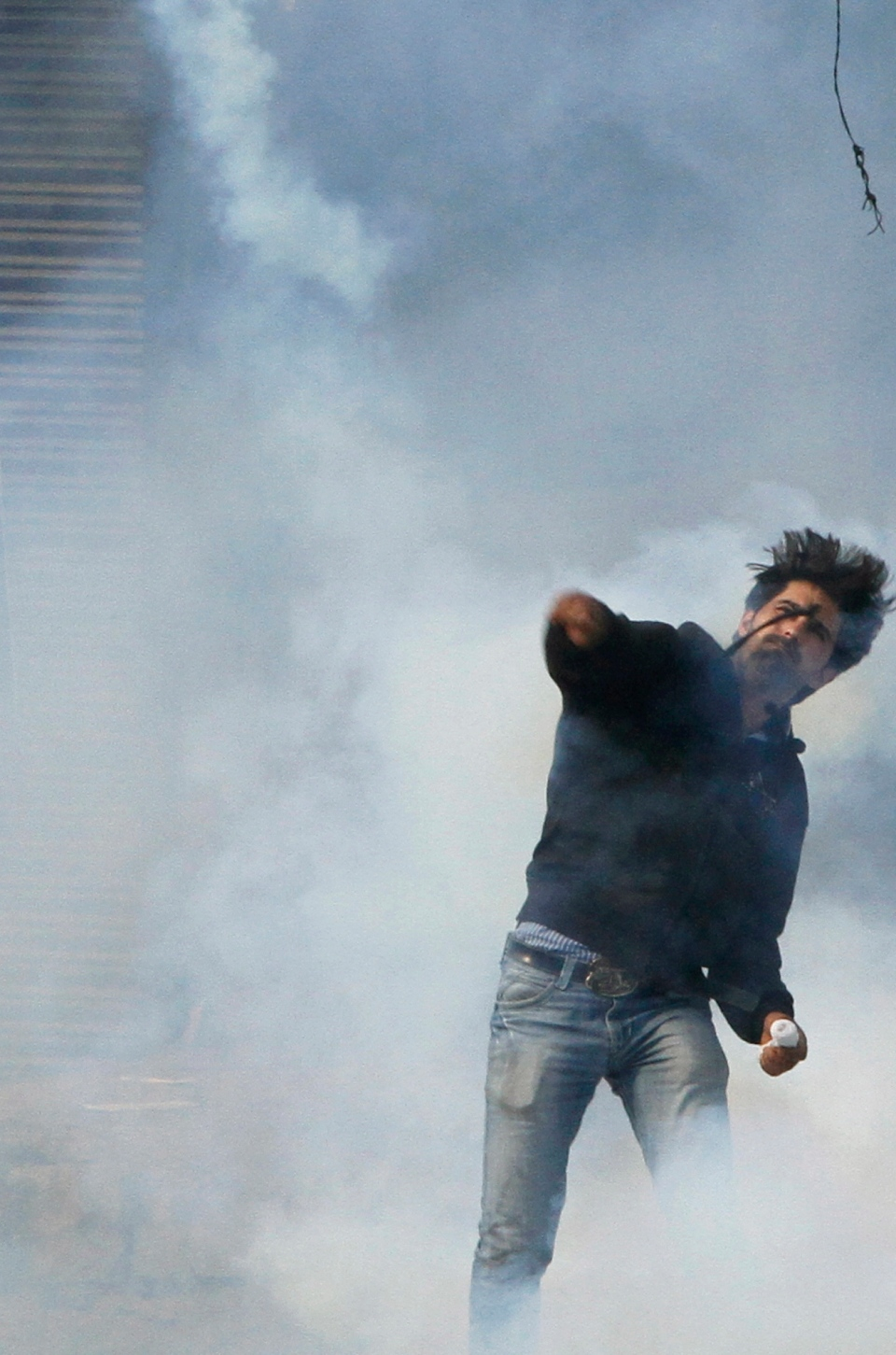 A Kashmiri Shiite Muslim throws back an exploded tear gas shell at Indian policemen after being stopped by police during a Muharram procession in Srinagar, India, Wednesday, Nov. 13, 2013. (AP / Mukhtar Khan)