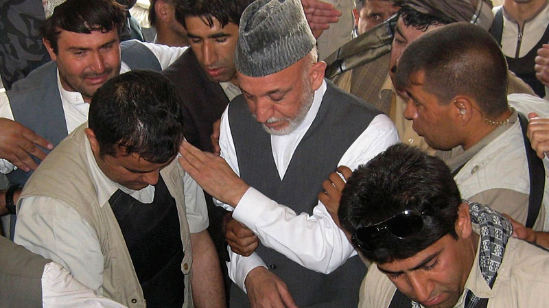 Afghan President Hamid Karzai, center, attends the burial of his half brother Ahmed Wali Karzai in his family's ancestral village of Karz, in Kandahar province, Afghanistan, Wednesday, July 13, 2011. (AP Photo)