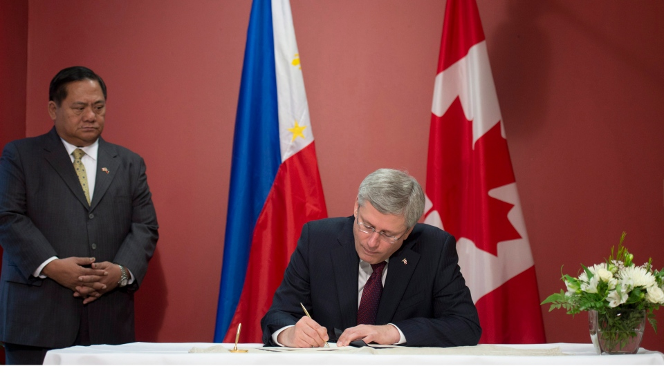 Leslie Gatan, Philippine Ambassador to Canada looks on as Canadian Prime Minister Stephen Harper signs the Book of Condolences at the Embassy of the Republic of the Philippines Wednesday November 13, 2013 in Ottawa. (Adrian Wyld / THE CANADIAN PRESS)