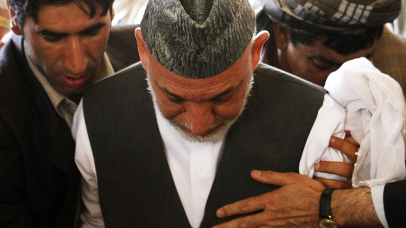 Afghan President Hamid Karzai centre, attends the burial of his half brother in his family's ancestral village of Karz, in Kandahar province, Afghanistan,Wednesday, July 13, 2011. (AP )