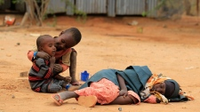 A Somali girl sleeps on the ground as other children play while waiting to register as refugees, in Ifo Camp, outside Dadaab, Kenya, Thursday, July 14, 2011. (AP/ Rebecca Blackwell)