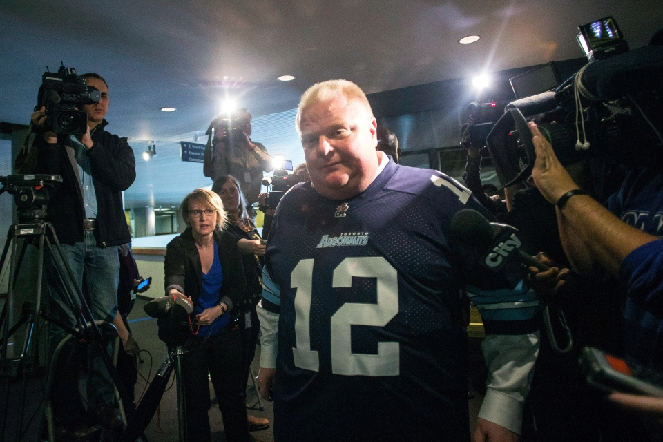 Toronto Mayor Rob Ford wears a Toronto Argonauts football jersey as he makes his way through the media outside his office on Thursday, Nov. 14, 2013. (Chris Young / THE CANADIAN PRESS)